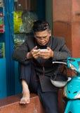 河内,越南- 2014年11月16日:老人读新闻并且听到音乐由从一个智能手机的耳机在吊Khay s的边路 库存图片