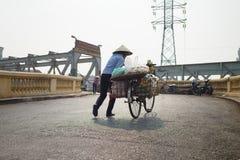 河内,越南- 2015年10月25日:设法妇女的供营商推挤她的果子在长的比恩桥梁的散漫的街道装载了自行车 免版税库存照片