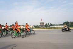 河内,越南- 2016年10月16日:越南女孩穿传统长的礼服Ao去由在河内街道上的出租机动三轮车pedicab的戴 免版税库存图片