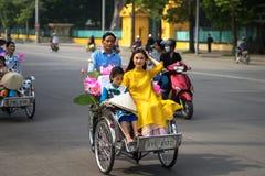 河内,越南- 2016年10月16日:越南女孩穿传统长的礼服Ao去由在河内街道上的出租机动三轮车pedicab的戴 免版税库存照片