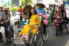 河内,越南- 2016年10月16日:越南女孩穿传统长的礼服Ao去由在河内街道上的出租机动三轮车pedicab的戴 库存照片