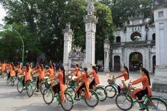 河内,越南- 2016年10月16日:越南女孩穿传统长的礼服Ao循环在河内街道上的戴 在foregrou的古庙 库存照片