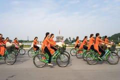 河内,越南- 2016年10月16日:越南女孩穿传统长的礼服Ao循环在河内街道上的戴 平方胡志明的陵墓 免版税图库摄影