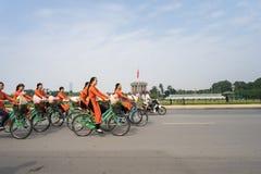 河内,越南- 2016年10月16日:越南女孩穿传统长的礼服Ao循环在河内街道上的戴 平方胡志明的陵墓 免版税库存照片