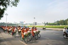 河内,越南- 2016年10月16日:越南女孩穿传统长的礼服Ao循环在河内街道上的戴 平方胡志明的陵墓 库存照片