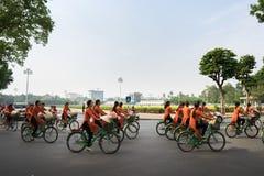 河内,越南- 2016年10月16日:越南女孩穿传统长的礼服Ao循环在河内街道上的戴 平方胡志明的陵墓 免版税库存图片