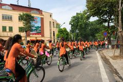 河内,越南- 2016年10月16日:越南女孩穿传统长的礼服Ao循环在河内街道上的戴 免版税库存照片