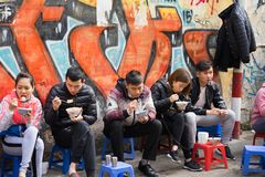 河内,越南- 2016年2月28日:顾客有他们的在街道货摊的膳食 吃在边的可口食物的京族爱 库存照片