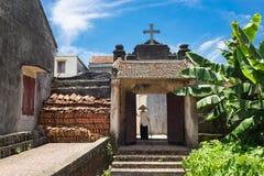 河内,越南- 2016年7月17日:有圣洁十字架的年迈的教会门在上面、越南老妇人穿戴圆锥形帽子和棍子走的i 库存图片