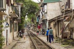 河内,越南- 2014年5月:穿过贫民窟的火车 库存图片