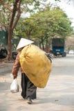 河内,越南- 2014年1月19日,贫穷的妇女回归家在一天劳方以后 库存图片