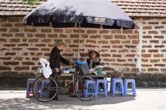 河内,越南- 2916 7月16, :销售炖果子的妇女,在摊位的变甜的粥谈话与老人,在backgro的老砖 库存图片