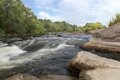 河南部的臭虫在夏天-岩石岸、急流、快速的河流程、鲜绿色的植被和多云蓝天 免版税库存照片