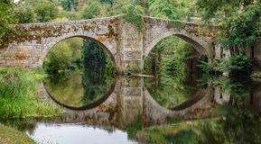 河和中世纪桥梁在阿利亚里斯,奥伦塞,西班牙 库存图片
