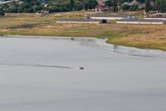 河和村庄看法  在河漂浮有两条鱼的小船 免版税库存图片