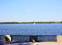 河和航行船的堤防在河 免版税库存照片