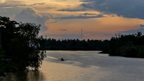 河在与一点小船风帆的乡区,日落期间 免版税库存图片