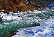 河在雪下的冬天 免版税库存图片