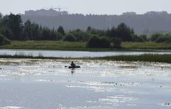 河在黎明和一位渔夫的剪影一条小船的在距离 天空的反射在水中 背景, ple 免版税库存图片