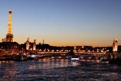 河塞纳河巴黎在与亚历山大III桥梁和艾菲尔铁塔的夜之前照亮了法国 免版税库存照片