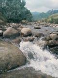 河岩石和多云天 免版税库存图片