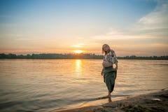河岸海滩的一名怀孕的美丽的妇女微笑与她的有爱和关心的mehandi装饰品腹部的 免版税库存图片
