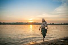 河岸海滩的一名怀孕的美丽的妇女微笑与她的有爱和关心的mehandi装饰品腹部的 库存照片