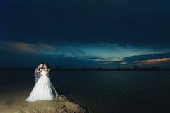 河岸的新婚佳偶在晚上 库存图片