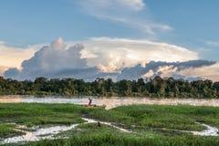河岸的未知的人,在村庄附近 日落,天的结尾 2012年6月26日在村庄,新几内亚,印度尼西亚 库存图片