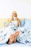 河床咖啡杯坐的妇女 免版税库存照片