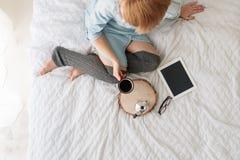 河床咖啡饮用的妇女年轻人 压片个人计算机,玻璃,有咖啡壶的木盛肉盘在床上 免版税库存照片