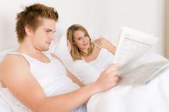 河床夫妇听音乐放松对年轻人 库存图片
