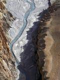 河床是从高度从上面拍摄的山小河:在高登上的陡峭的银行的中蓝色射流 免版税图库摄影