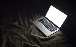 河床膝上型计算机 在家运作与copyspac的夜概念图象 库存照片