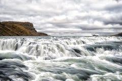 河急流在雷克雅未克,冰岛 水射流 水在多云天空落 速度和动荡 分行烘干前景深绿色横向山本质河河沿浅通配 库存图片