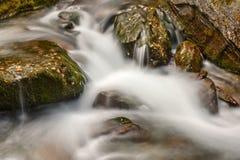 河水向青苔瀑布扔石头 库存照片