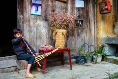 河江市,越南, 2017年11月14日, :弹奏一台传统仪器,北越南的Hmong年轻人 库存照片