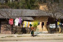 河江市,越南- 2016年2月14日:少数族裔山的Hmong房子与在她的ba的Hmong小女孩运载的圆白菜花 免版税库存图片