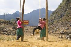 河江市,越南- 2014年2月7日:打摇摆比赛的未认出的Hmong孩子在操场在多山区域 库存图片