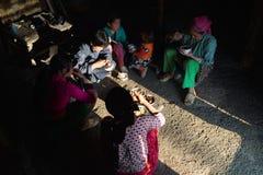 河江市,越南- 2016年2月13日:H ` mong少数族裔家庭吃午餐在他们的房子在日元Minh区,在太阳射线下 免版税库存照片