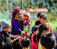 河江市,越南- 2018年11月08日:佩带Hmong传统新年的未认出的小组孩子穿衣,等待他们 库存图片