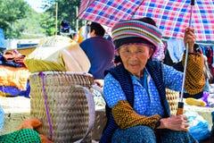 河江市,越南- 2015年11月08日:拿着她的婴孩后面的未认出的Hmong妇女,当回家在阳光下时 库存图片