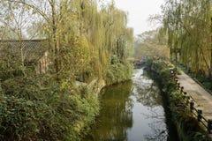 河沿古老豪宅在森林在晴朗的冬天中午 免版税库存照片
