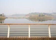 河沿扶手栏杆在晴朗的有雾的冬天planked人行桥 免版税库存图片
