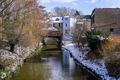 河流动在桥梁街道Frome下的Frome在多雪的天 免版税库存图片