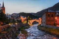 河流桥渡一个村庄在一个五颜六色的晚上 库存照片