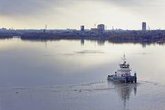 河猛拉在河转过来并且操纵反对一个大城市的背景 免版税库存照片
