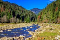 河由岩石岸流动在秋天山森林附近 免版税库存图片