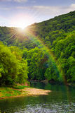 河由岩石岸流动在秋天山森林附近 免版税库存照片