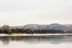 河的两座山背景在冬天 免版税库存图片